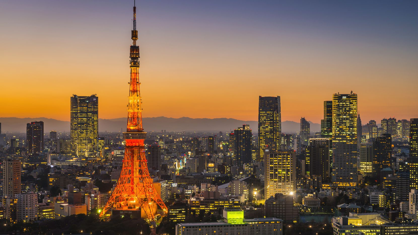 The iconic spire of Tokyo Tower spotlit above the twinkling lights and skyscrapers of downtown Tokyo below orange sunset skies, Japan. ProPhoto RGB profile for maximum color fidelity and gamut.