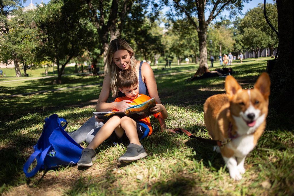 J.J. Wilhem, 6, reads The Adventures of Beekle: The Unimaginary Friend, by Dan Santat under the shade of a large oak tree on the south lawn of the Capitol with his stepmom Kate Wilhem and their 2-year-old corgi, Ginny Weasley, during the Texas Book Festival on Oct. 27, 2018 in Austin.