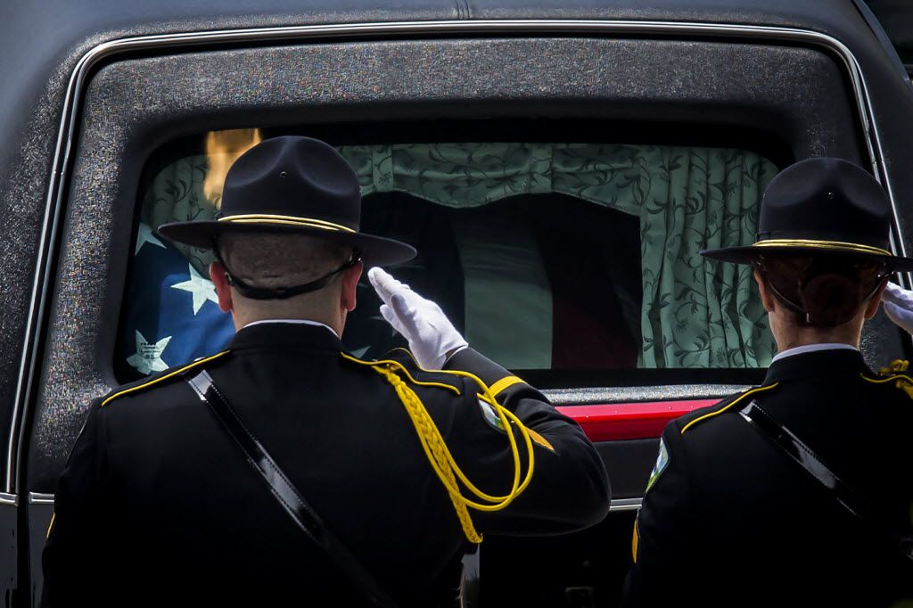 Law enforcement officers saluted the hearse carrying the casket of Dallas Police Officer Michael Krol after services at Prestonwood Baptist Church on Friday.