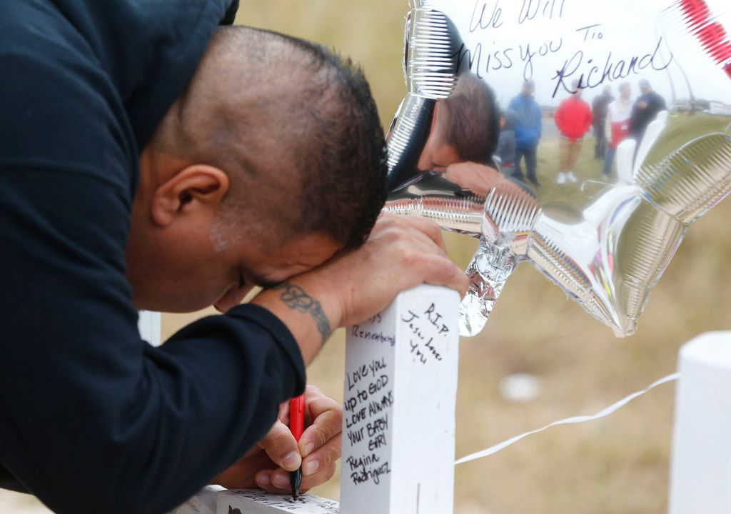 A mourne, who did not give his name, writes a message on a cross at a memorial in front of First Baptist Church in Sutherland Springs, Texas on Nov. 10, 2017. The church in Sutherland Springs, Texas was the site of a shooting that killed 26 parishioners and left 30 injured.