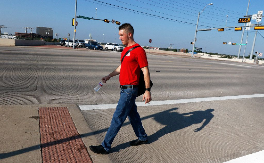 Corey Ahrens walks across U.S. 75 in Plano after leaving his home in Plano.