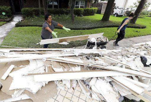 Adriana Pérez, a la izquierda, y Clair Hummel ayudan a retirar material dañado por las inundaciones por la tormenta Harvey en casa de unos amigos el miércoles en Houston. Foto AP