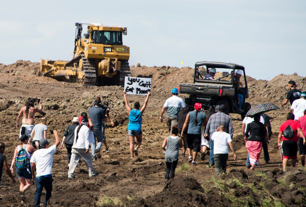 Native American protestors and their supporters are confronted by security during a demonstration against work being done for the Dakota Access Pipeline (DAPL) oil pipeline, near Cannon Ball, N. D., on Sept. 3. / AFP PHOTO / Robyn Beck