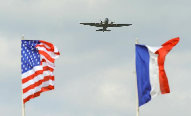 An American and a French flag are seen in the foreground as a C-47 military transport airplane flies over Utah Beach in Sainte-Marie-du-Mont, northern France on the eve of the 70th anniversary of the World War II Allied landings in Normandy.