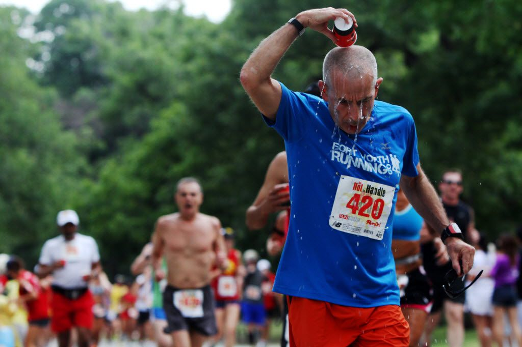 Paul Johnson, of Arlington, pours cool water on his head during a Too Hot to Handle race at White Rock Lake.