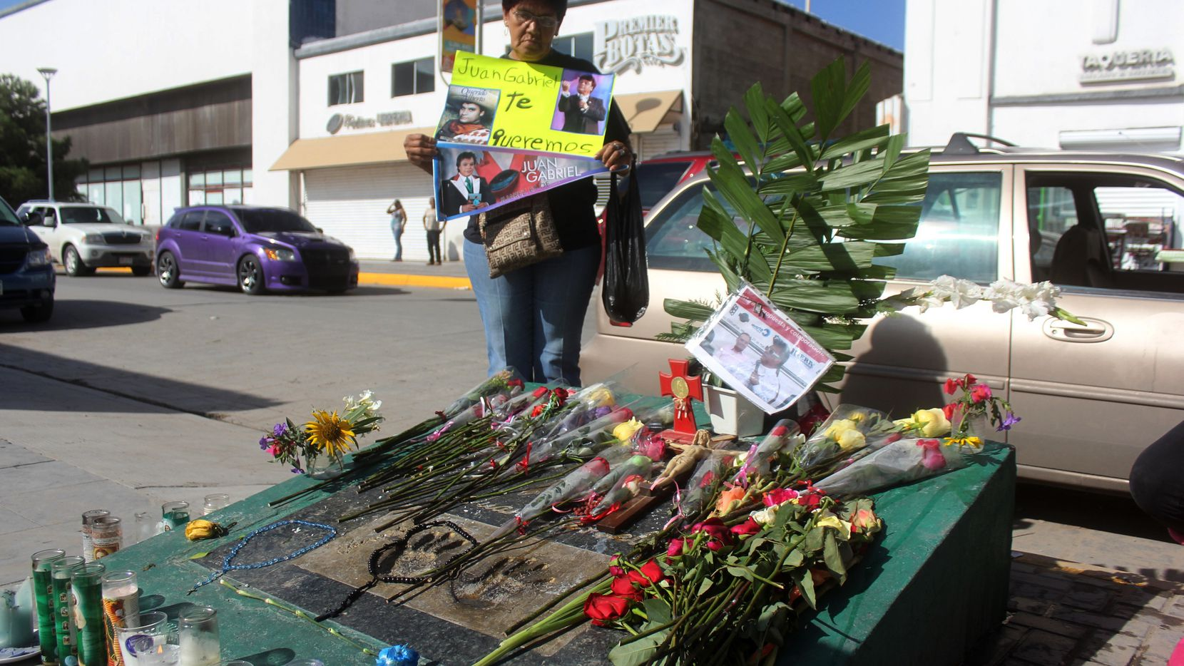 Una mujer sostiene un cartelón con un mensaje de aprecio al cantante Juan Gabriel en Ciudad Juárez. (AP)