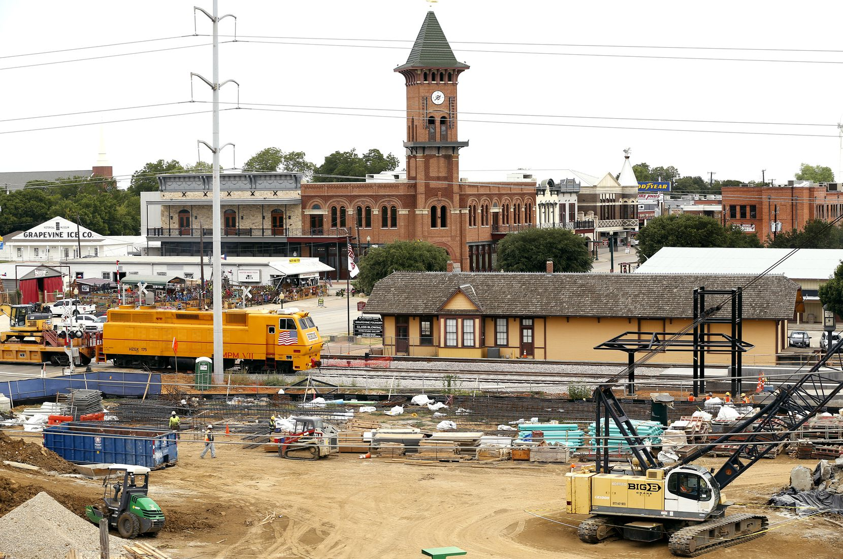 A railroad maintenance train passes the historic Grapevine train depot in downtown Grapevine.   Development around the TexRail commuter line connecting downtown Fort Worth with Grapevine and DFW Airport includes the 121-room Hotel Vin and 552-space parking garage.