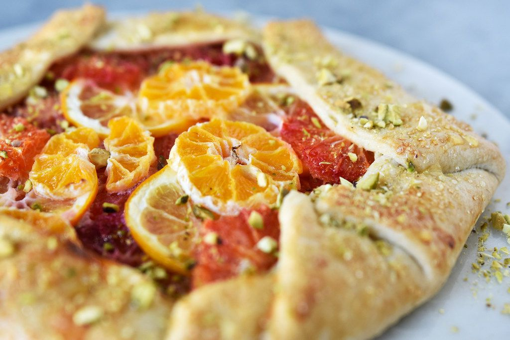 Rustic citrus galette gets a sprinkling of sugar for sweetness and a scattering of pistachios to add crunch.