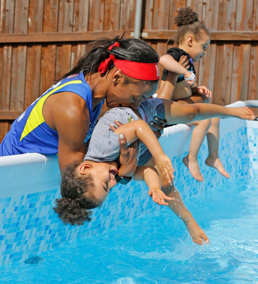 Dallas Wings' player Glory Johnson plays with her twin daughters Solei, left, and Ava in their backyard pool at their home in Arlington, Texas, on Saturday, June 30, 2018. (Louis DeLuca/The Dallas Morning News)