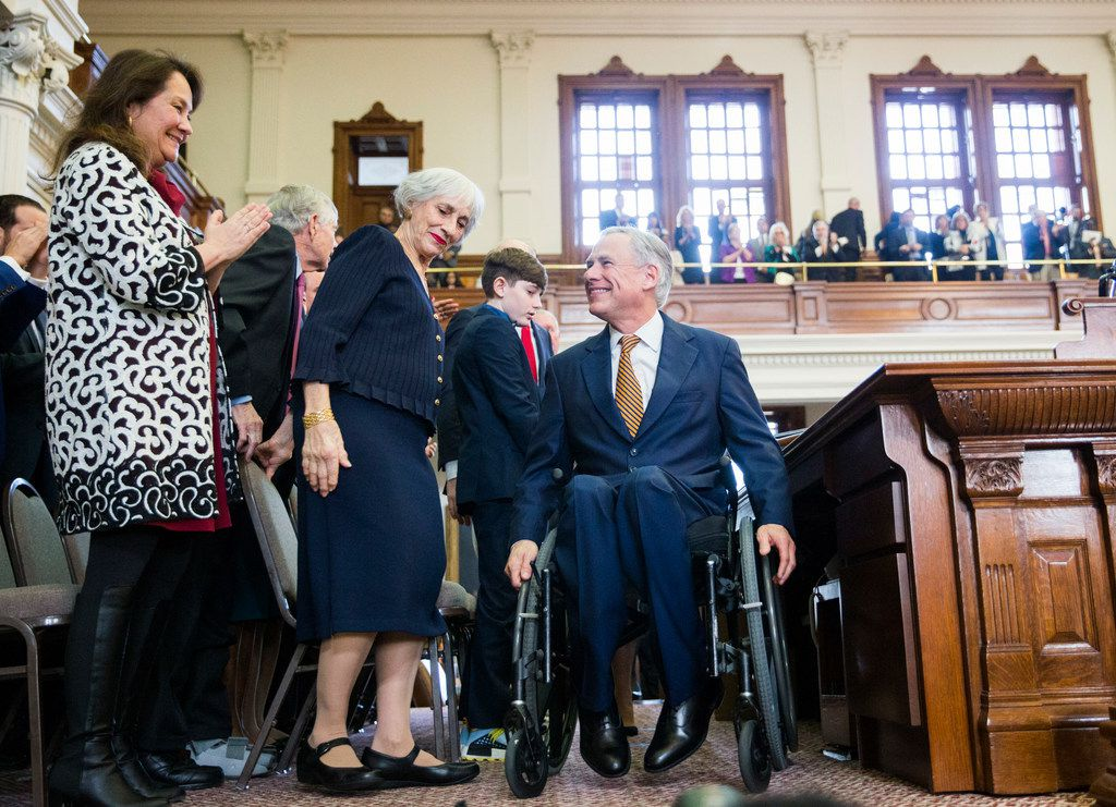 As Texas first lady Cecilia Abbott (left) looked on, Gov. Greg Abbott wheeled himself off the House dais after speaking at the installation of new House Speaker Dennis Bonnen on Tuesday. Bonnen's mother, Matina Bonnen, is at center.