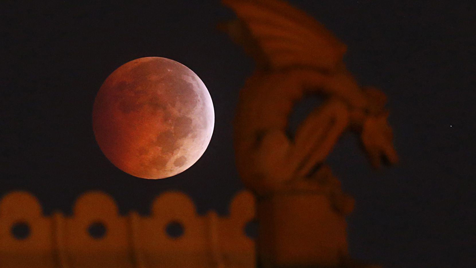 A blood moon appears behind a gargoyle atop the old red Dallas County Courthouse during a lunar eclipse in Dallas in 2014.