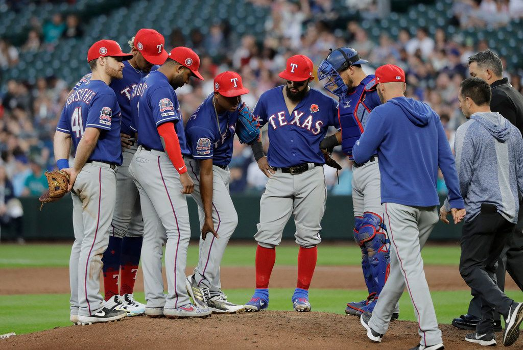 Texas Rangers relief pitcher Jose Leclerc, fourth from left, holds his right leg as members of the Rangers' training staff arrive, at right, during the seventh inning of a baseball game against the Seattle Mariners, Monday, May 27, 2019, in Seattle. Leclerc left the game with the injury. (AP Photo/Ted S. Warren)