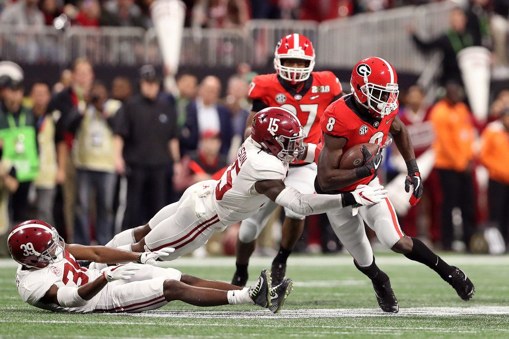 ATLANTA, GA - JANUARY 08: Riley Ridley #8 of the Georgia Bulldogs is tackled by Ronnie Harrison #15 of the Alabama Crimson Tide on a run during the first quarter in the CFP National Championship presented by AT&T at Mercedes-Benz Stadium on January 8, 2018 in Atlanta, Georgia.  (Photo by Christian Petersen/Getty Images)
