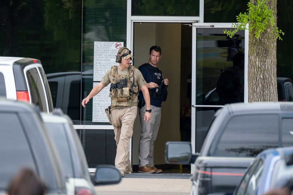 On April 3, U.S. Immigration and Customs Enforcement officials stand outside CVE Group in Allen. Immigration agents arrested nearly 300 people at the North Texas technology company in what authorities say is one of the largest enforcement actions of its kind in a decade (Smiley N. Pool/The Dallas Morning News via AP)