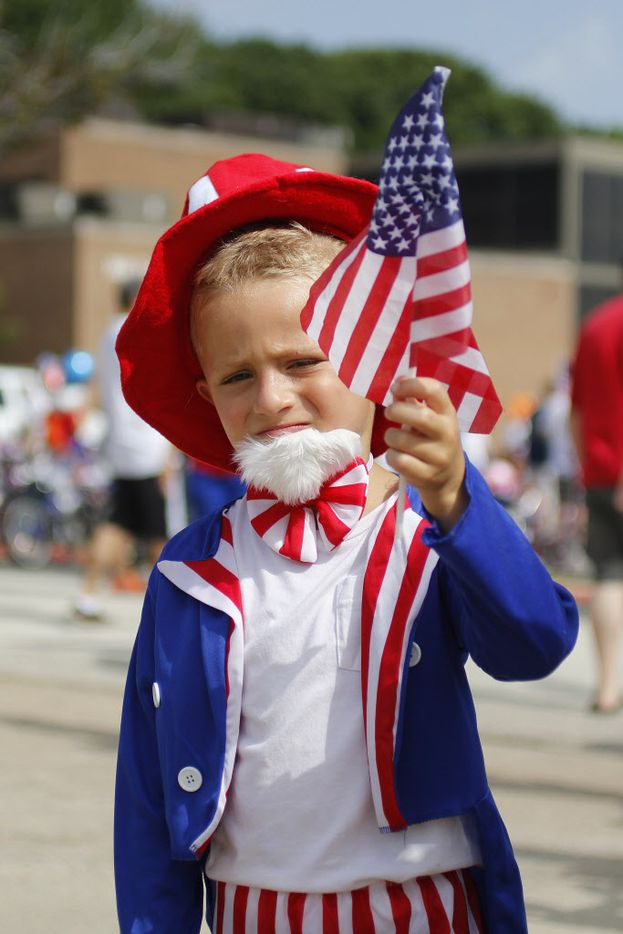 Dylan Laroche, 5, waves his American flag during the Independence Fest Children's Parade in Flower Mound, Texas on Saturday, July, 4, 2015.