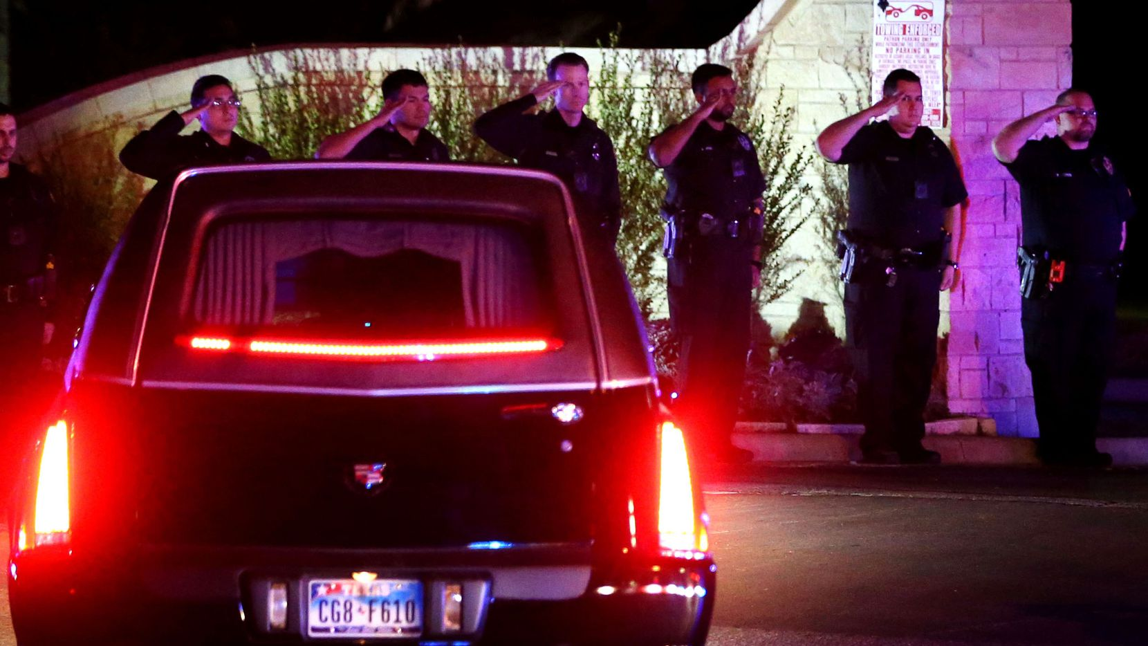 Dallas police officers salute the body of slain Richardson police officer David Sherrard as it is escorted into Restland Memorial Park in Dallas on Thursday, Feb. 8, 2018. Sherrard was fatally shot after responding to a disturbance at an apartment complex in Richardson, Texas on Wednesday, Feb. 7, 2018.