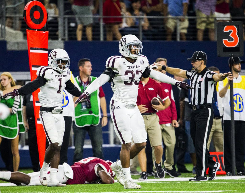 Texas A&M Aggies defensive back De'Vante Harris (1) and Texas A&M Aggies linebacker Shaan Washington (33) signal in incomplete pass on third down by Arkansas Razorbacks during overtime of their game on Saturday, September 26, 2015 at AT&T Stadium in Arlington, Texas.   (Ashley Landis/The Dallas Morning News)