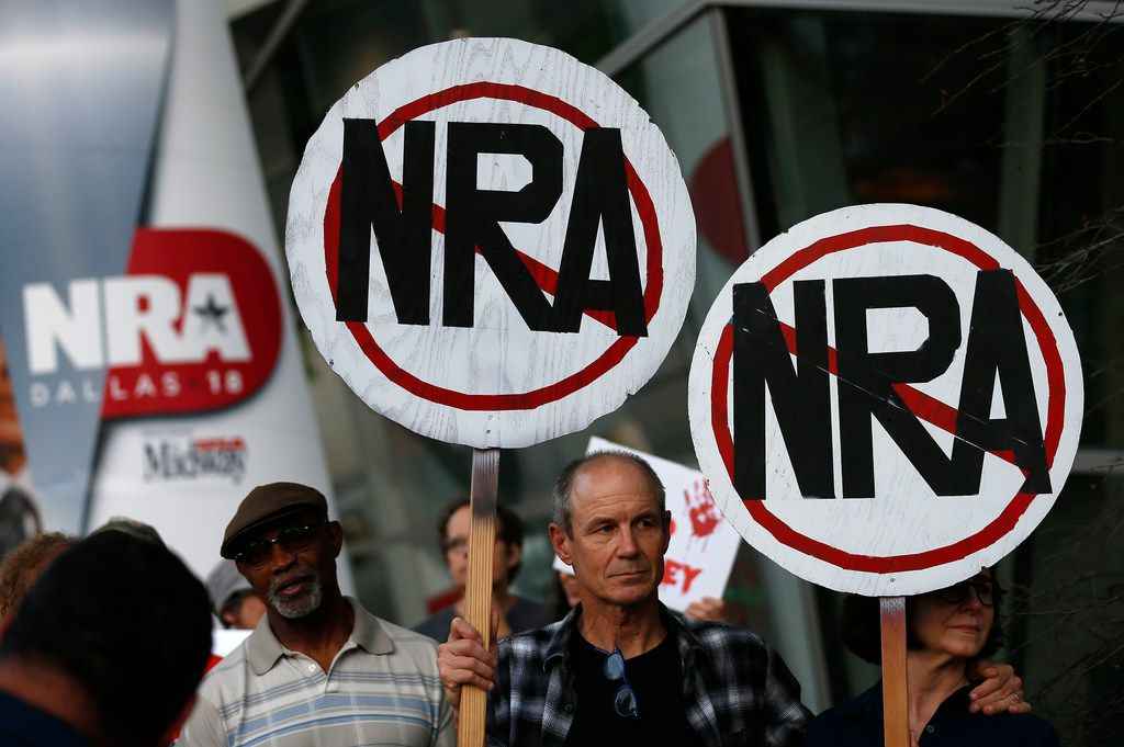 Protesters Carin Hughes, right, and her husband Jon Kieffer hold signs protesting against the NRA outside their convention.