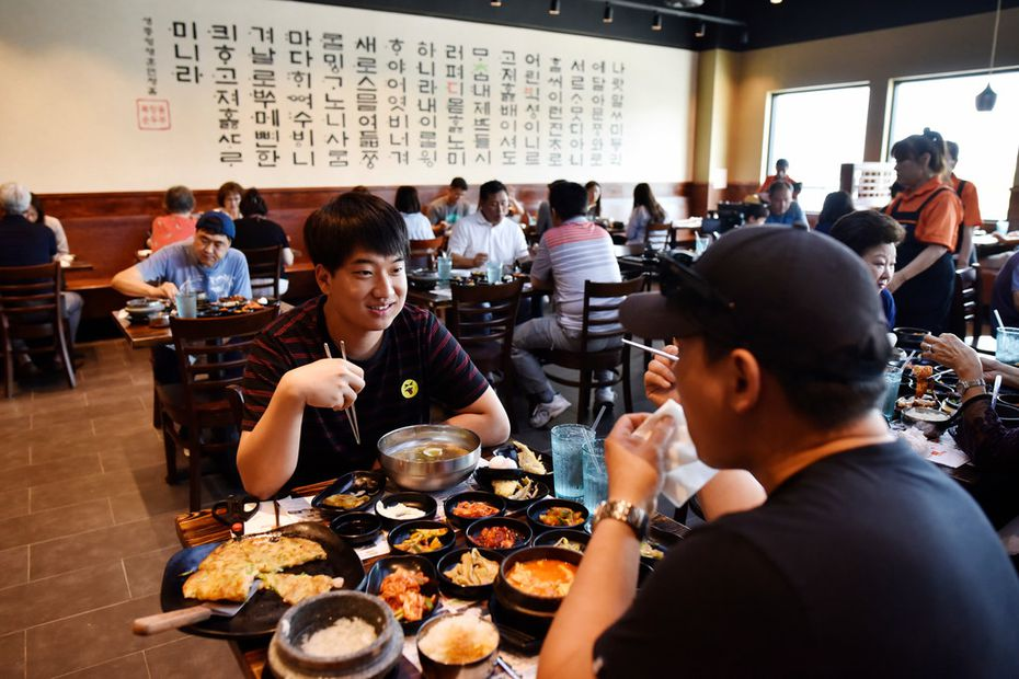 Chan Woo, 22, and Andy Kin, 46, both of Lewisville, enjoy lunch at BCD Tofu House in Carrollton on July 1, 2019.
