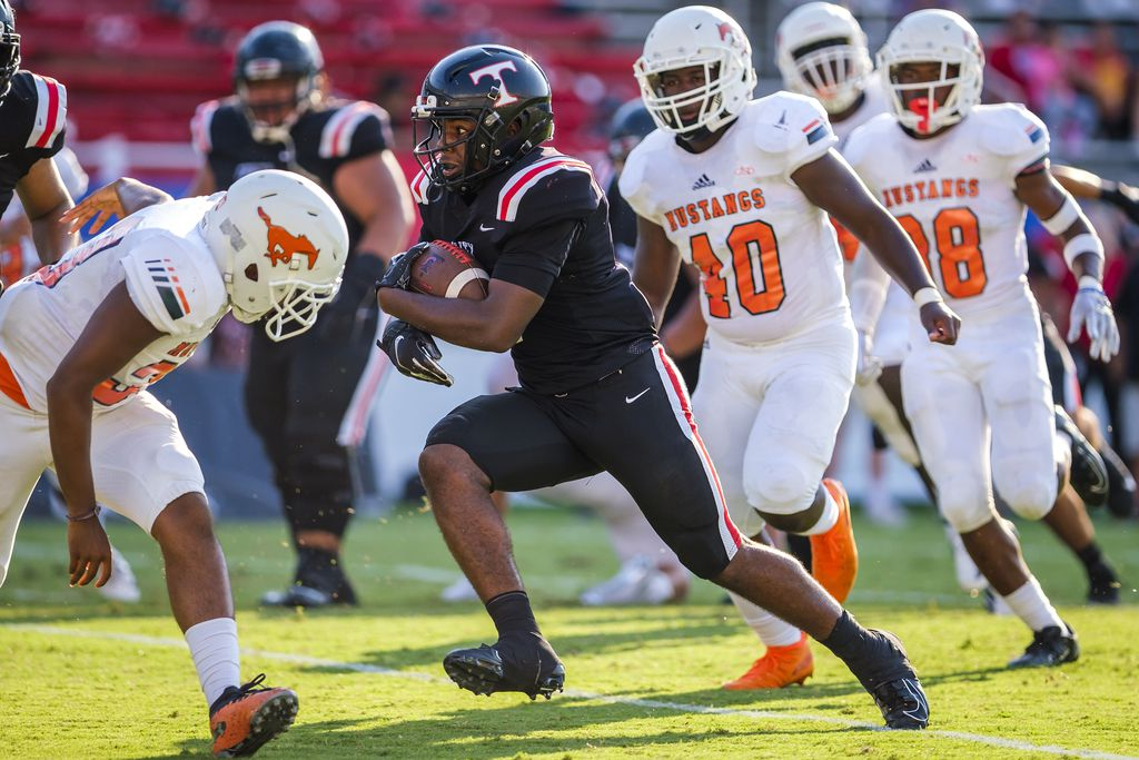 Euless Trinity running back AJ Barnett (5) breaks through the Sachse defense on his way to a touchdown during the first half of a high school football game at the Cotton Bowl on Friday, Sept. 6, 2019, in Dallas. (Smiley N. Pool/The Dallas Morning News)