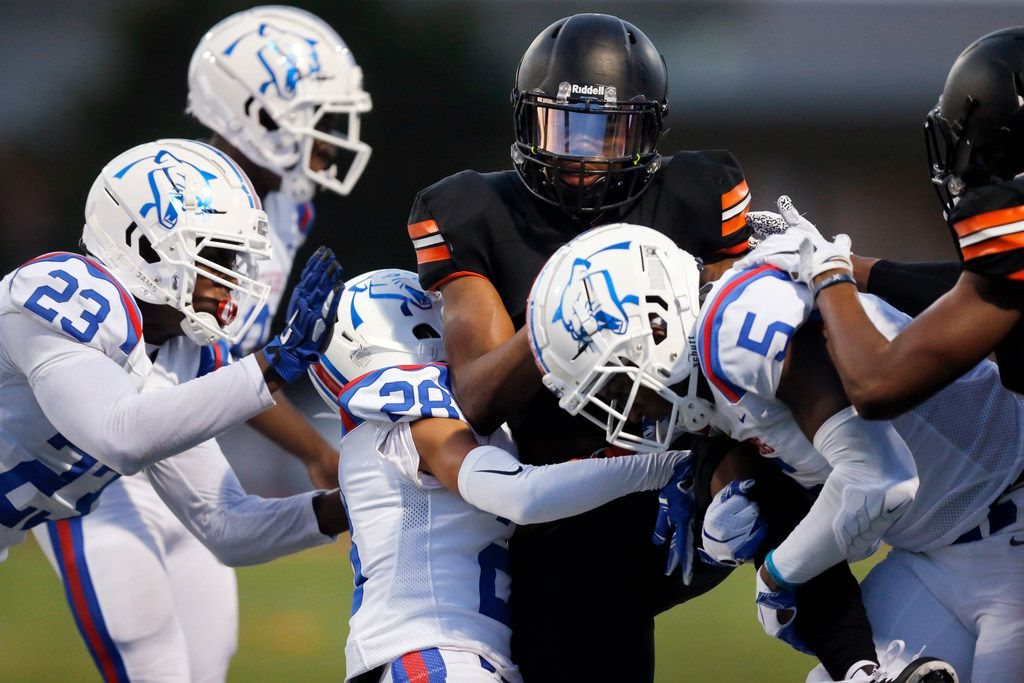 Lancaster running back Tre Bradford (2) is wrapped up by Duncanville defenders Omari Abor (23), Awtavius Griffin (28) and Christopher Thompson (5) during a first half run at Beverly D. Humphrey Tiger Stadium in Lancaster Texas, Friday, August 30, 2019. (Tom Fox/The Dallas Morning News)