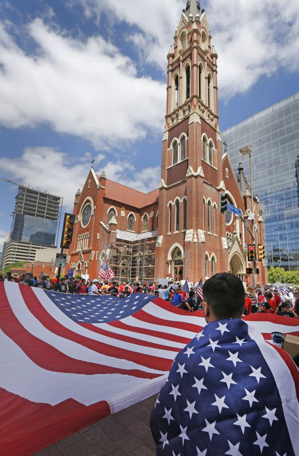 Christopher Rodriguez of Oak Cliff helps hold a large flag as he and others get ready for the Mega March, which started at the Cathedral Shrine of Our Lady Guadalupe in downtown Dallas, photographed on Sunday, April 9, 2017. (Louis DeLuca/The Dallas Morning News)