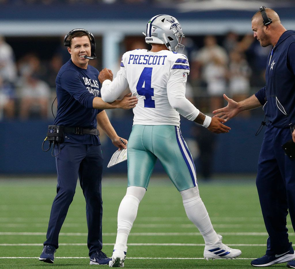 Dallas Cowboys offensive coordinator Kellen Moore (left) and offensive line coach Marc Colombo (right) celebrate with Dallas Cowboys quarterback Dak Prescott (4) after a touchdown during the second half of play at AT&T Stadium in Arlington, Texas on Sunday, September 8, 2019. Dallas Cowboys defeated the New York Giants 35-17 in the home opener.