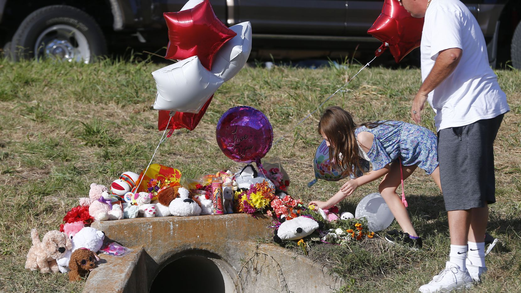 Miley Grahmann, 8, with her father Patrick Grahmann, leaves a bear with a jar of Carmex (in case her lips get chapped in heaven) in the area where the body of Sherin Mathews was found.