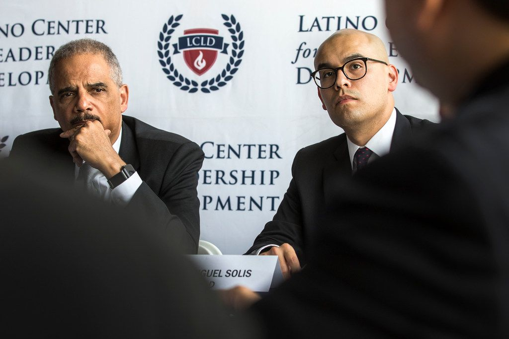 Former U.S. Attorney General Eric Holder (left) and Miguel Solis, president of the Latino Center for Leadership Development and a Dallas school board member, listened to a speaker at the center in Dallas on Tuesday.