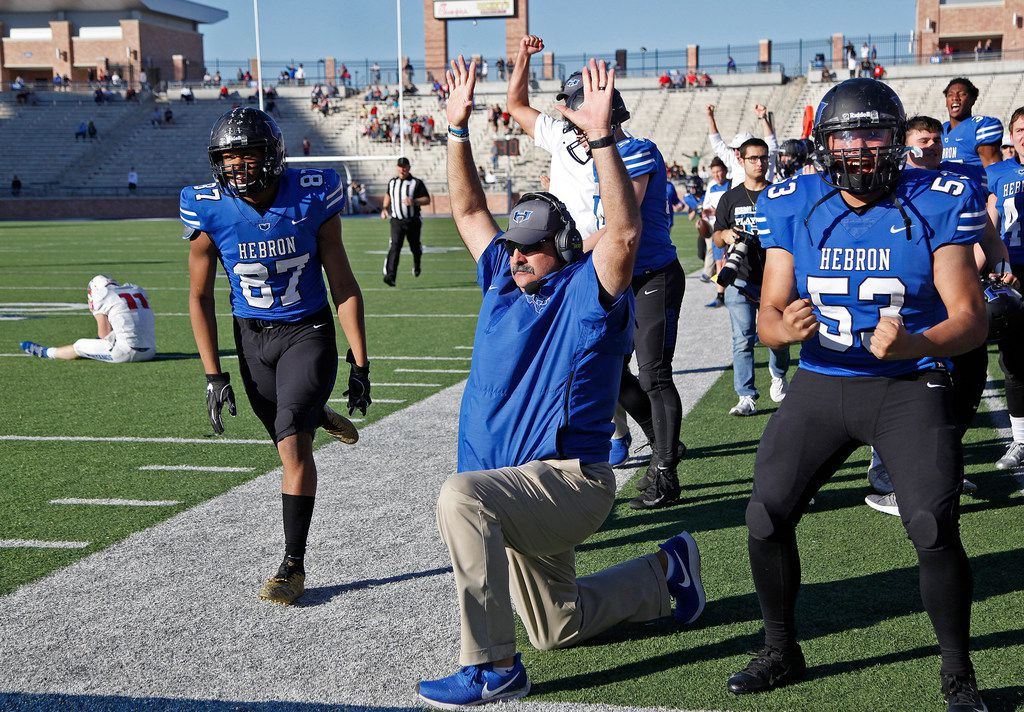 Players on the Hebron sideline erupt around head coach Brian Brazil as they watch an interception returned for a touchdown to put the game away during the fourth quarter as Pearce High School hosted Hebron High School in a Class 6A Division II Region I area-round playoff game at Eagle Stadium in Allen on Friday, November 23, 2018.  (Stewart F. House/Special Contributor)