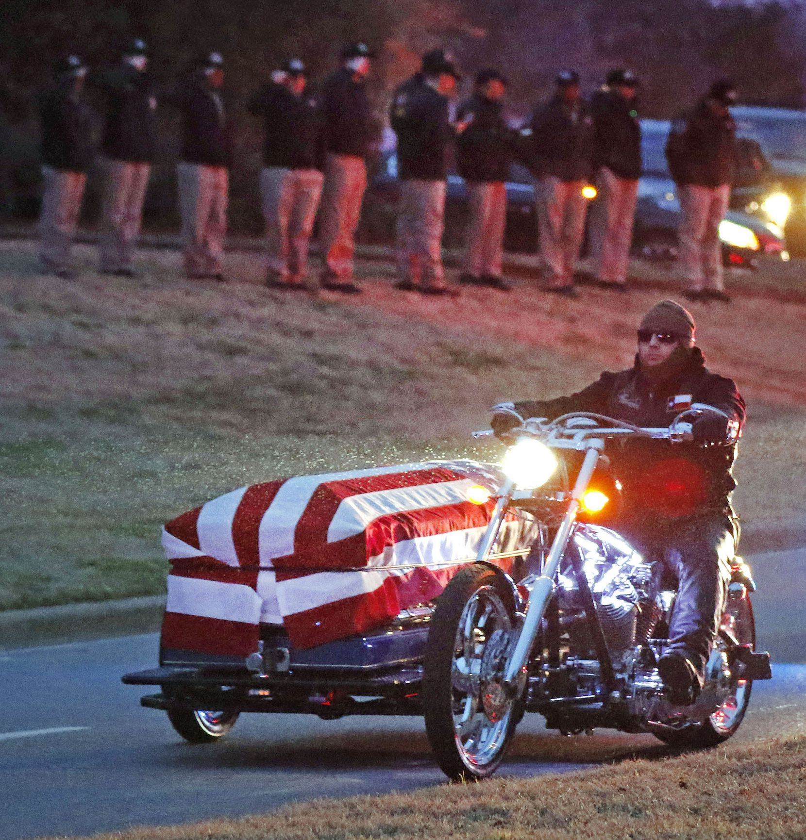 Officers solemnly salute as a motorcycle carries the body of Richardson police officer David Sherrard in a flag-draped casket en route from a church service to his burial, in Dallas, Texas, Tuesday, February 13, 2018. Sherrard was fatally shot a week before.