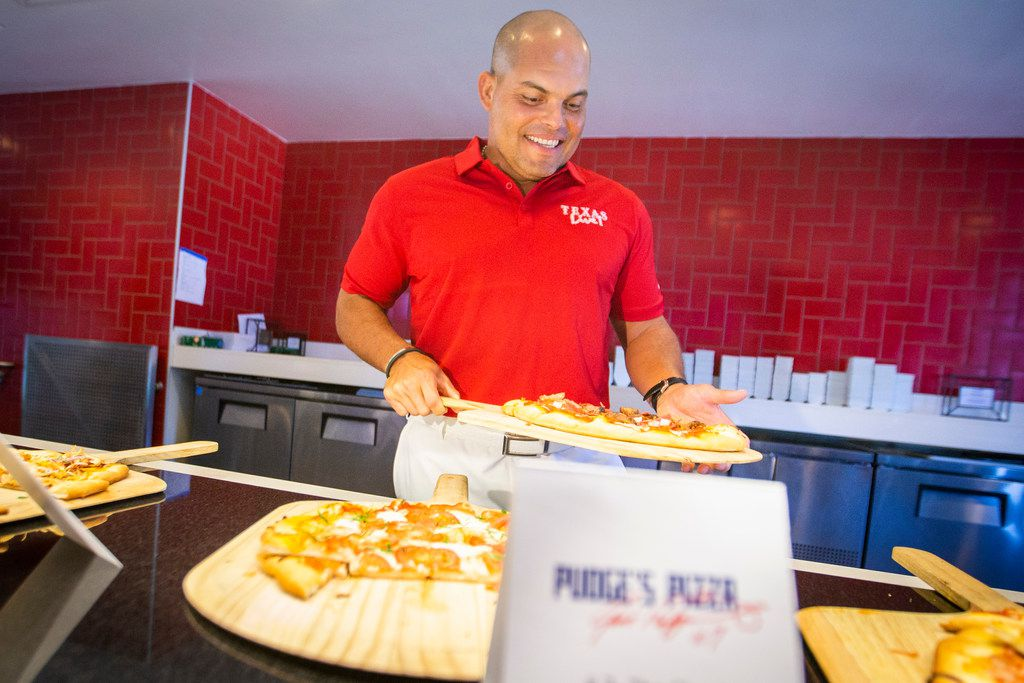 "Hall of Fame Texas Rangers catcher Ivan ""Pudge"" Rodriguez shows off samples of pizza that will be offered at Pudge's Pizza."