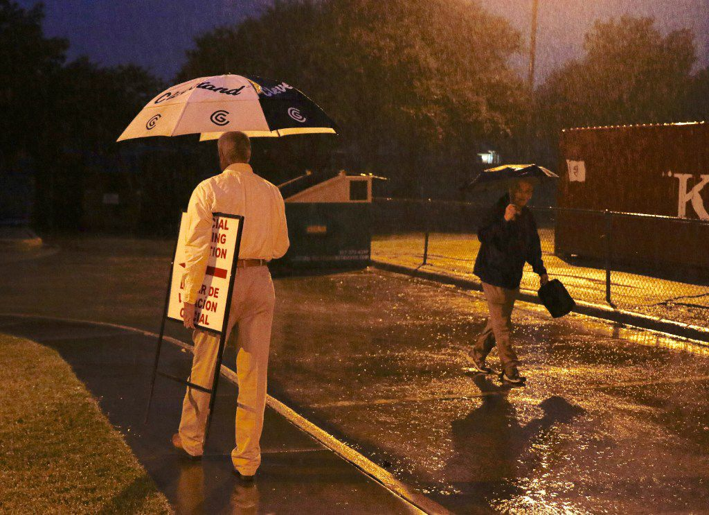 Election clerks Jimmy Murphy, left, carries a polling sign in the rain at Yale Elementary School in Richardson as Edward Miller walks toward the gymnasium on Tuesday, November 8, 2016 before voters arrived. (David Woo/The Dallas Morning News)