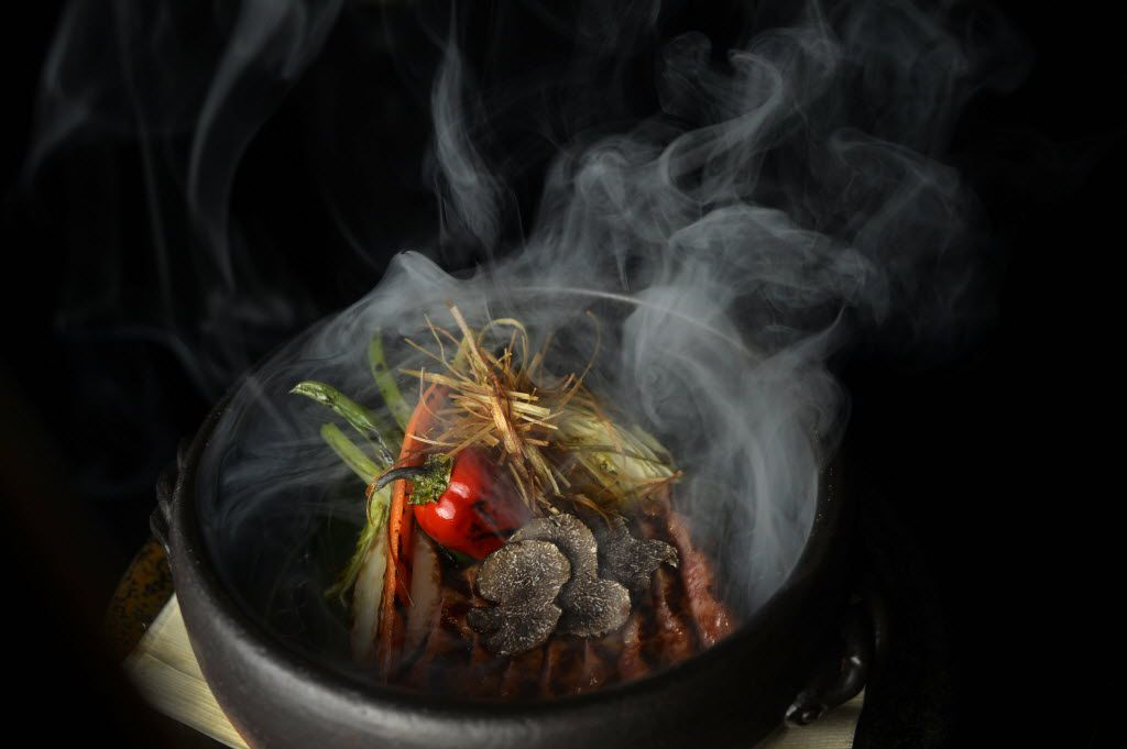 Wagyu beef from Japan's Miyazki prefecture comes to the table smoking over cherry wood in a clay pot , with shaved black truffles and charred cabbage.