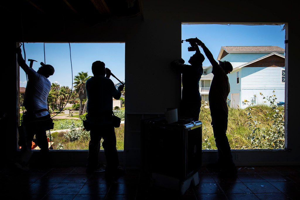 Workers replace windows on a home on South 12th Street that remains vacant nearly a year after Hurricane Harvey slammed ashore in the Texas Gulf Cost city of Port Aransas.