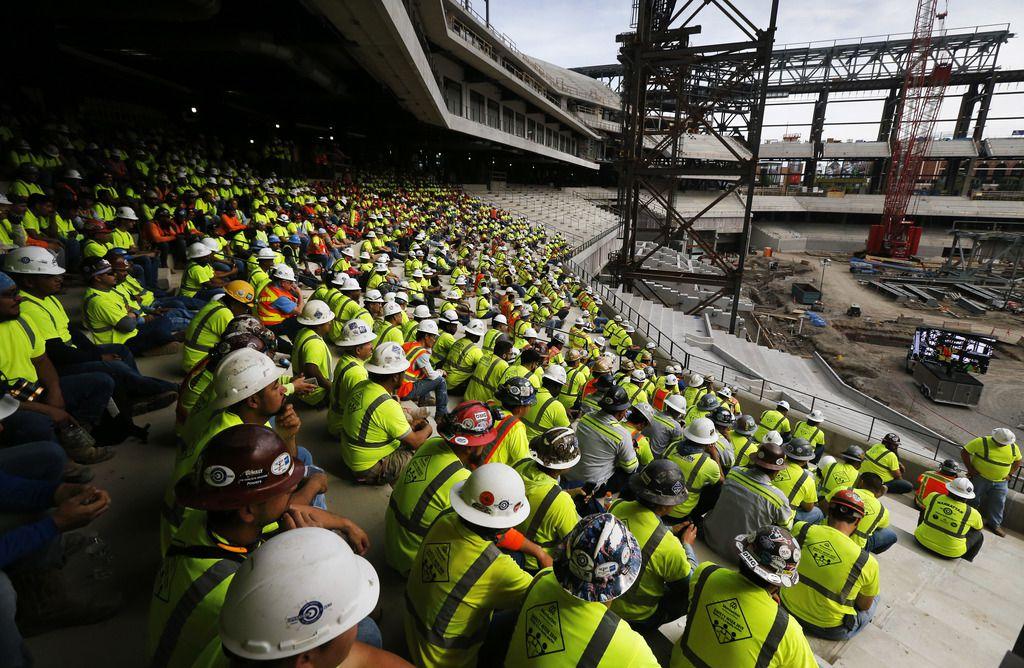 Grupos de trabajadores de construcción en el nuevo estadio de los Rangers, aún en construcción.