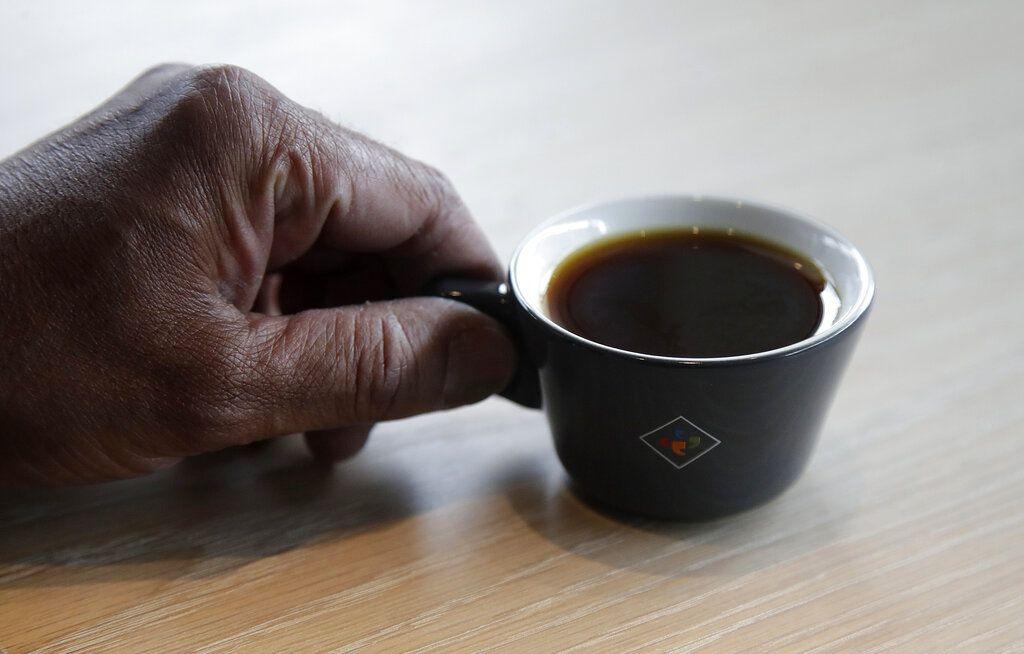 Bo Thiara, propietario de Klatch Coffee, sostiene una taza del café Elida Natural Geisha en su tienda en San Francisco, el miércoles 15 de mayo de 2019. Cada taza vale 75 dólares. (AP Foto/Jeff Chiu)