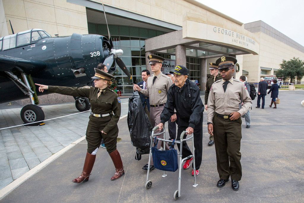 World War II veterans pass a 1943 Grumman TBM Avenger, the same type plane former President George H.W. Bush was shot down in during the war, as they arrive for a 75th Anniversary of Pearl Harbor commemoration at the George Bush Presidential Library on Wednesday, Dec. 7, 2016, in College Station, Texas.  (Smiley N. Pool/The Dallas Morning News)