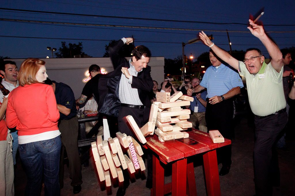 Travis Francis, left, Taylor Shaver, Pat Sheehan, Dan Basso and Dave Basso play a giant Jenga game during one of Systemware's quarterly meetings.