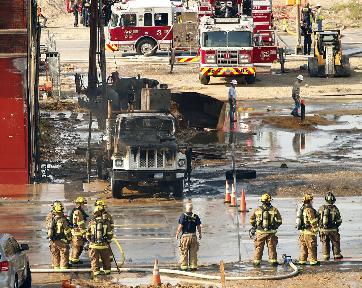 Dallas firefighters looked at the charred drilling truck that was engulfed in flames after a ruptured gas line casued a fire at a construction site.