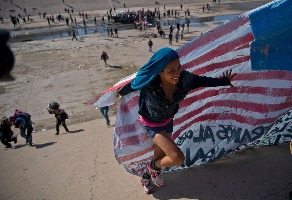 A migrant woman helps carry a handmade U.S. flag up the riverbank at the Mexico-U.S. border after getting past Mexican police at the Chaparral border crossing in Tijuana on Nov. 25, 2018, as a group of migrants tries to reach the U.S.