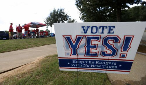 A sign of Vote Yes! Keep the Rangers is seen on Nolan Ryan Expressway as fans tailgate in the background before Game 1 of American League Division Series between Texas Rangers and Toronto Blue Jays at Globe Life Park in Arlington.
