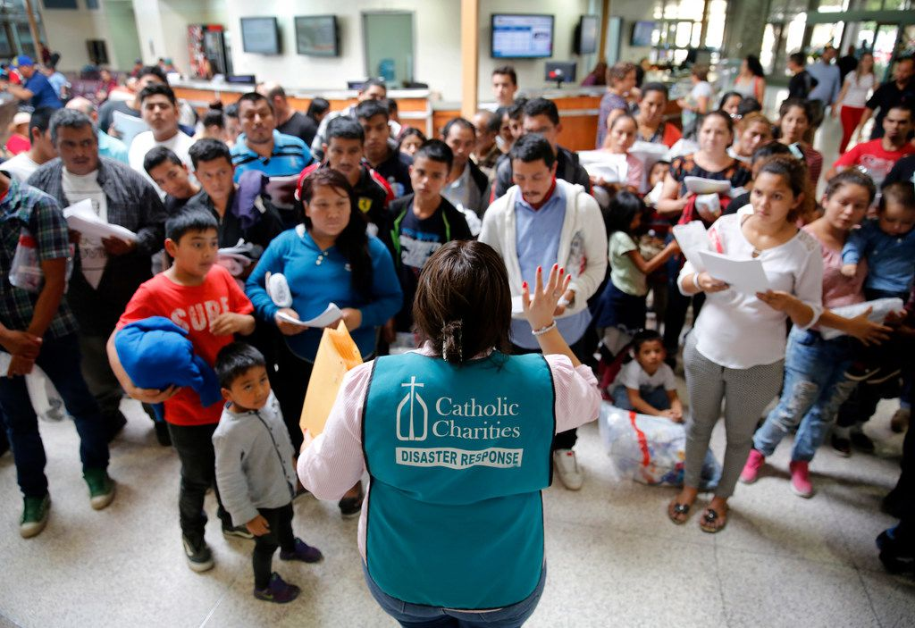 A staffer from the Catholic Charities of the Rio Grande Valley gives instructions to Central American immigrants who were dropped off on government buses at the Central Station bus terminal in downtown McAllen, Texas, Sunday, June 24, 2018.  The migrants were processed by the U.S. Border Patrol.  The families were rounded up and sent to a Catholic Charities shelter.