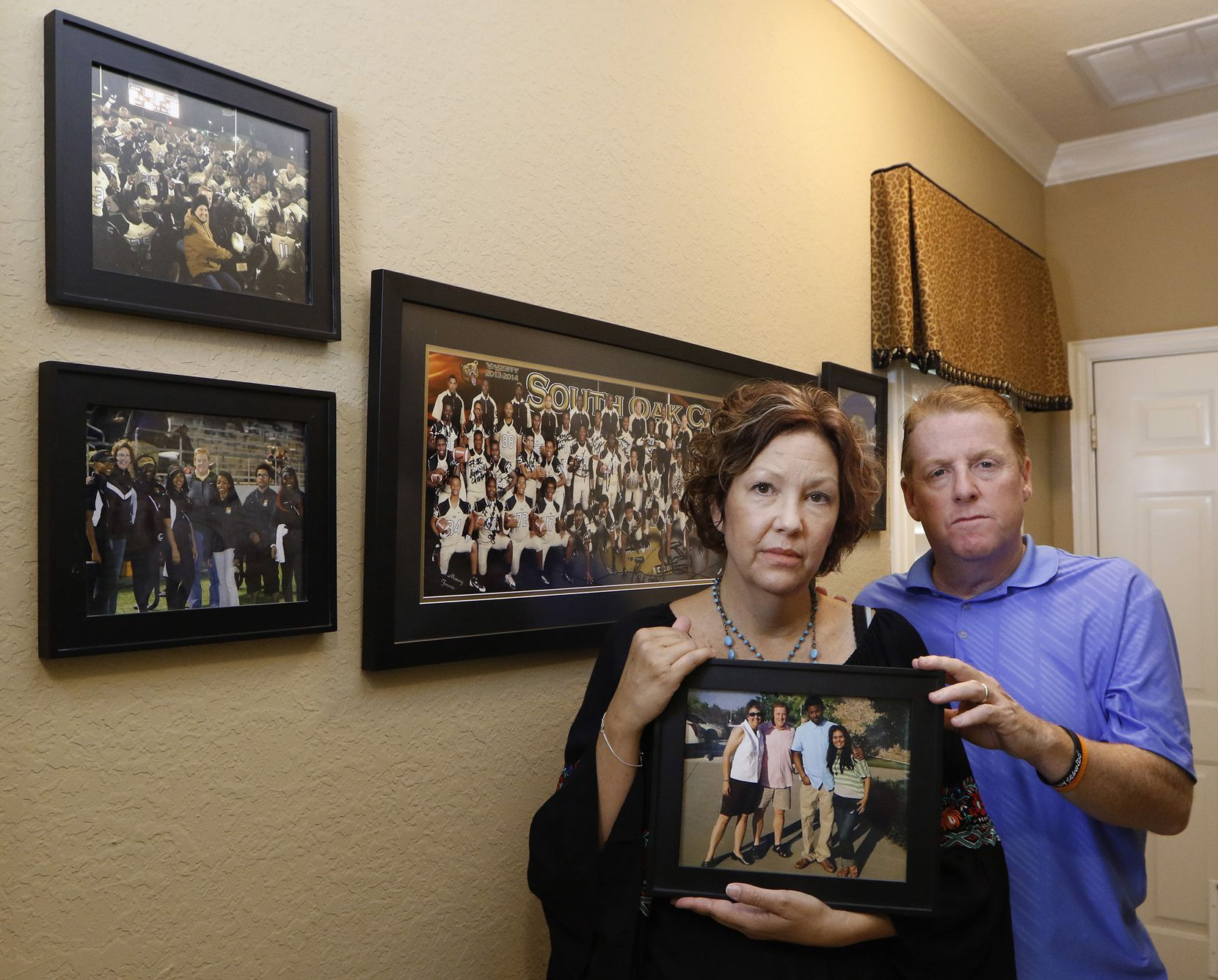 Lisa and Dave Stephenson hold a photograph of them with Thomas Johnson and Maria Paula in their home in Farmersville, Texas on Thursday, June 30, 2016. The photo was taken at their church in Plano in July 2014. Thomas Johnson, former Skyline and Texas A&M football star stayed as a guest in their home. Dave and his wife tried to rehabilitate Johnson before the murder of David Stevens while he was running at White Rock Lake on Oct. 12, 2015. (David Woo/The Dallas Morning News)