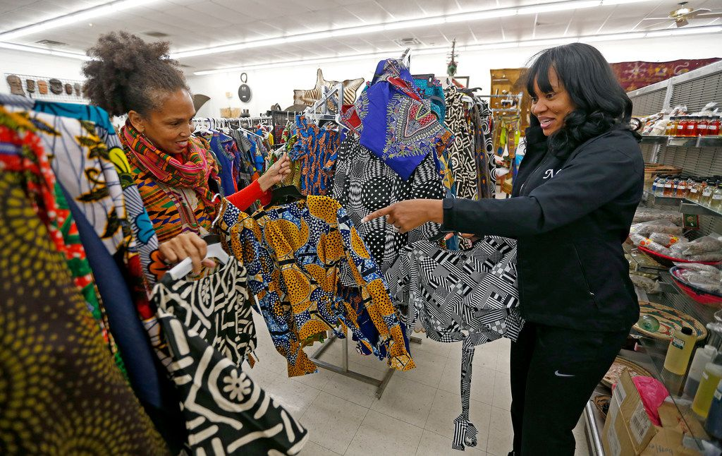 Owner Akwete Tyehimba, left, shows her regular customer Nia Khepera some dresses at Pan-African Connection in Dallas in February 2018.