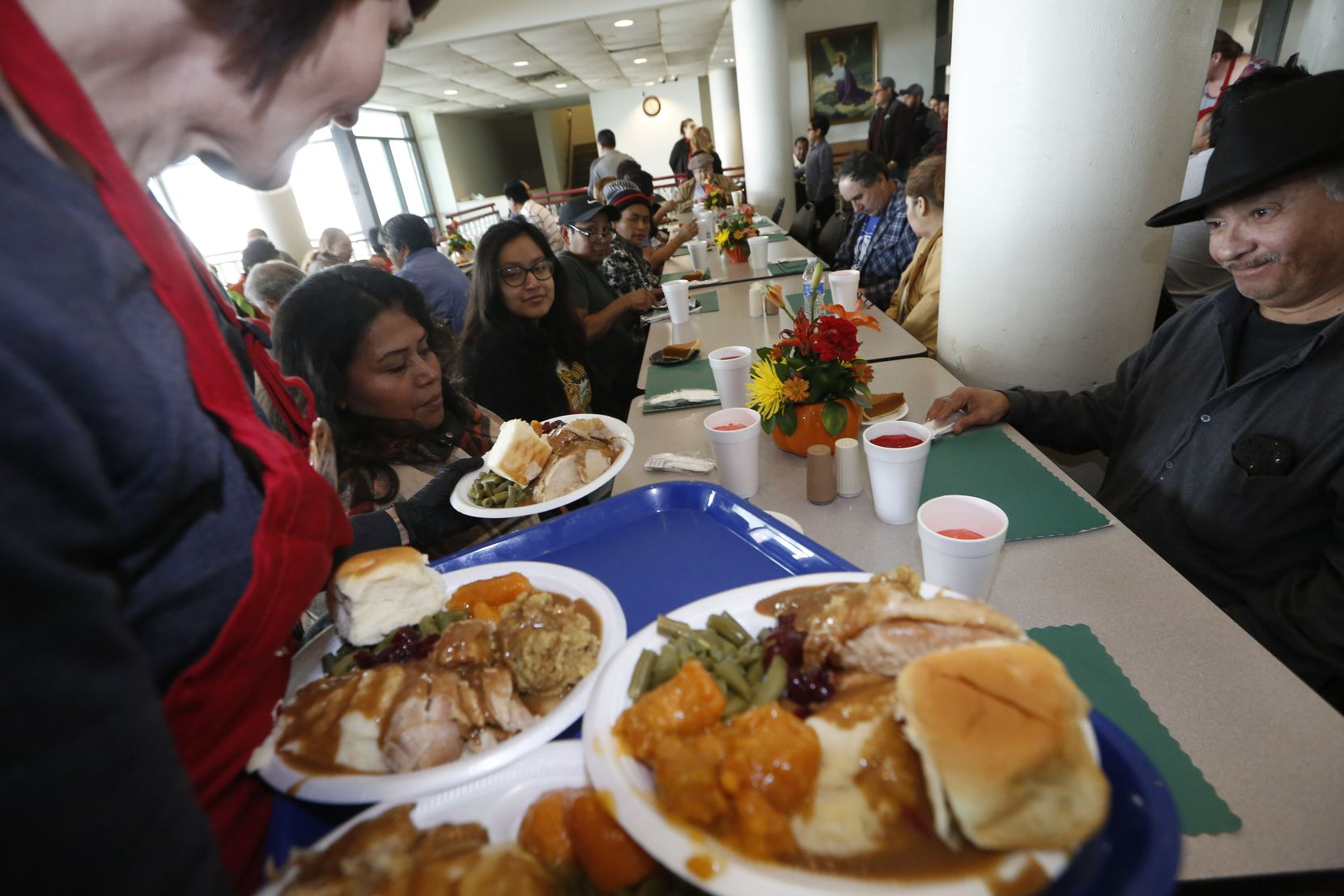 From left: Jacqueline Gonzalez, Sara Carlos and Vincent Camacho are served their Thanksgiving meal at The Salvation Army in Dallas last November.