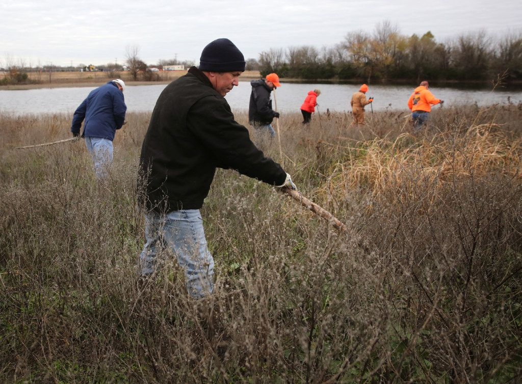 Mark Morris used a stick to move brush during a weekly search for the remains of his daughter, Christina Morris, in an area of northern Collin County on Dec. 10, 2016.