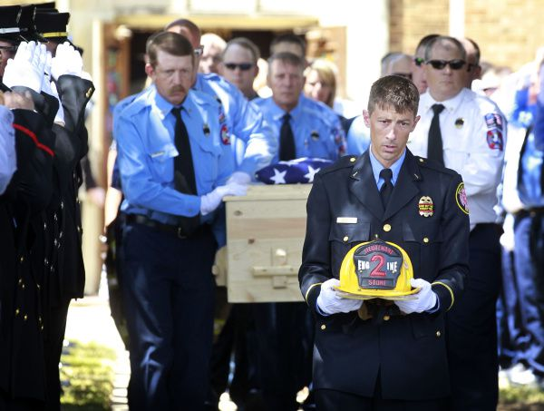 Brownwood Fire Department Lt. G. Neson carries the helmet of Lt. Shannon Stone ahead of pallbearers carrying the casket at Stone's funeral Monday in Brownood. Stone died Thursday after falling from the stands at Rangers Ballpark in Arlington.