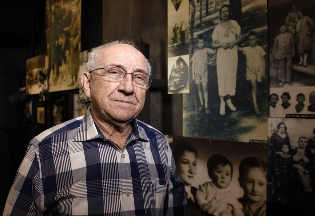 Max Glauben in front of some of the photographs taken of him and his mother and brother in Poland at the Dallas Holocaust Museum/Center for Education.