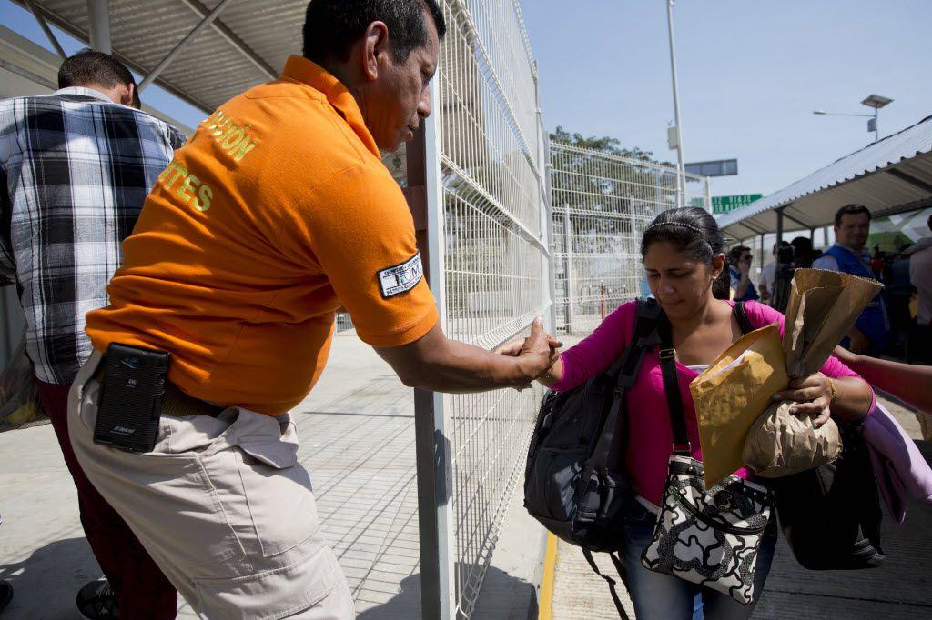 Un agente mexicano de Migración ofrece ayuda a una inmigrante cubana que llegó a Ciudad Hidalgo, Chiapas, en la frontera con Guatemala.  (Moisés Castillo/AP)